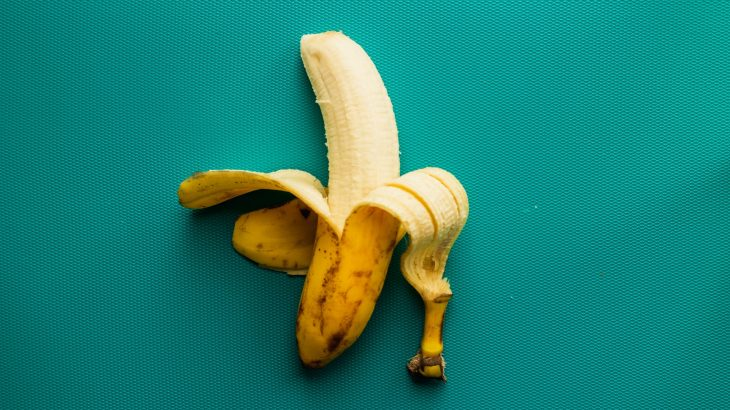 A half peeled banana on a turqoise background.