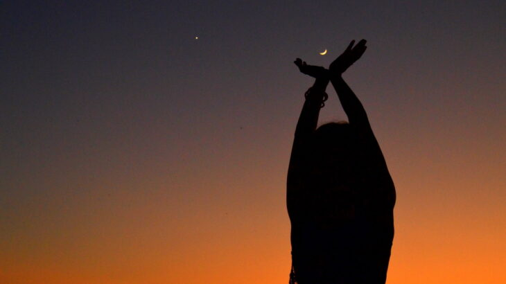 A silhouette of a person with their arms raised against a night sky, the moon seeming to be cupped in their hands.